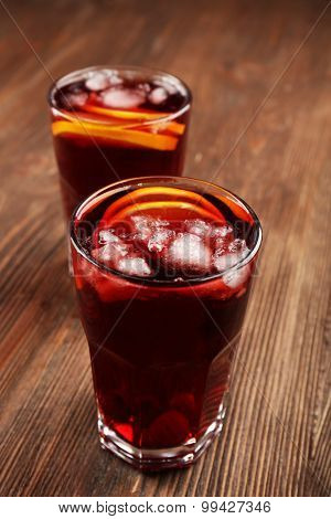 Glasses of cherry juice on wooden background