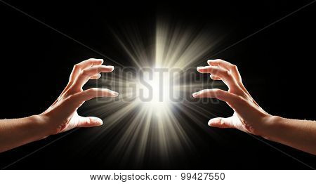 Human hands with light on black background