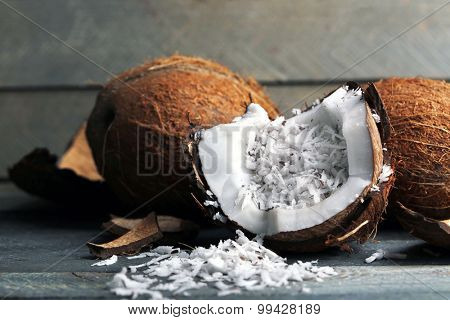 Coconut shavings in coconut on wooden background