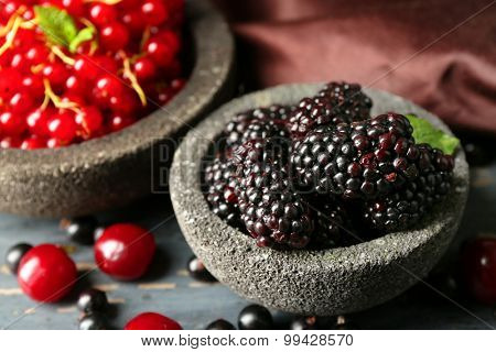 Forest berries in bowls on wooden background