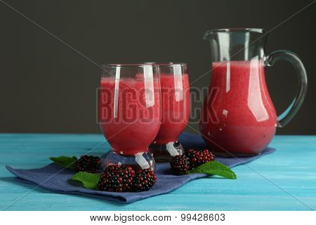 Glasses of blackberry smoothie on wooden table on grey background