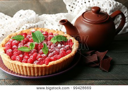 Tart with fresh raspberries and teapot, on wooden background
