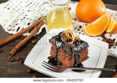 Portion of Cake with Chocolate Glaze and orange on plate, on wooden background