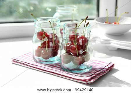 Cherries in glass jars, on light background