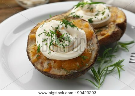 Baked potato with mayonnaise and herbs in white plate, closeup