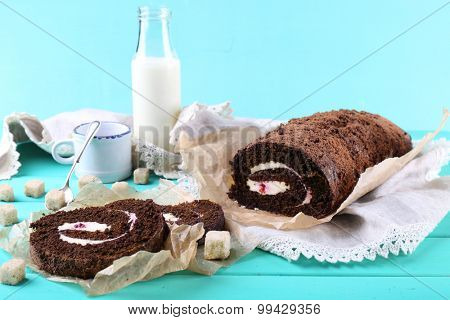 Delicious chocolate roll on wooden table, closeup