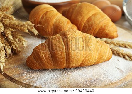 Fresh croissants with flour on wooden table, closeup