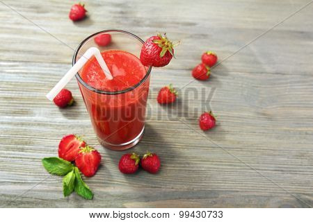 Glass of strawberry smoothie with berries on wooden table close up