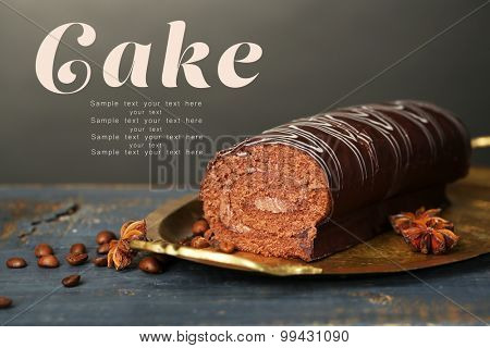 Delicious roll cake on wooden table, on dark background