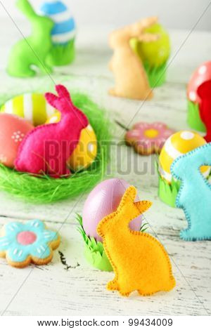 Handmade Easter Rabbits And Easter Eggs On White Wooden Background