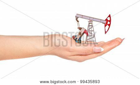 Female Hand Holding The Oil Pump. The Concept Of Oil Crisis
