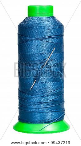 Sewing Spool With Blue Thread And Attached Needle
