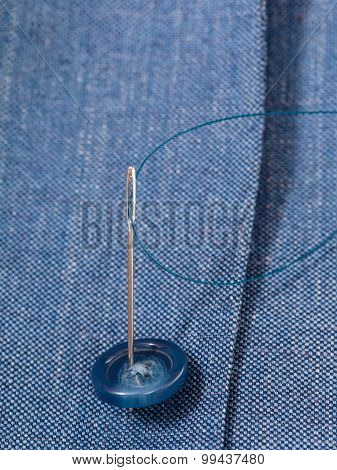 Attaching Of Button To Blue Silk Dress By Needle