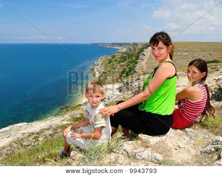 Mother And Children Sitting On The Edge