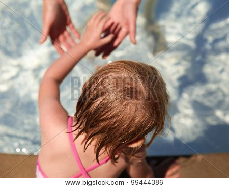 a small child reaching for her mother's hand in a local pool on a hot summer day