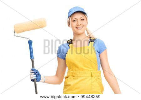 Young female house painter in a yellow overall holding a paint roller isolated on white background