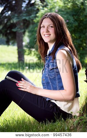 Young sexi female using tablet outdoor sitting on grass, smiling