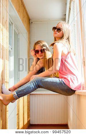 Two happy pretty teenage girls in sunglasses having fun