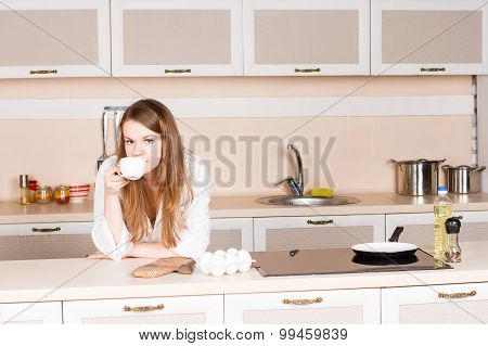 Girl A White Mens Shirt Is Drinking Tea Elbows On Table In Kitchen The Morning