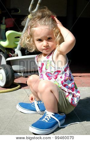 Young Girl In Adult's Blue Shoes.