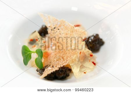 Small gourmet dish with black caviar, close-up