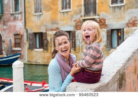 Laughing Mother Holding Happy Daughter Sitting Along Canal Edge