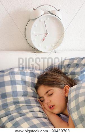 Girl Sleeping Near Huge Alarm Clock