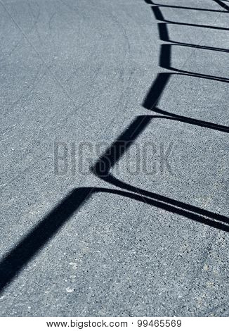 Shadow On Asphalt Road Railings