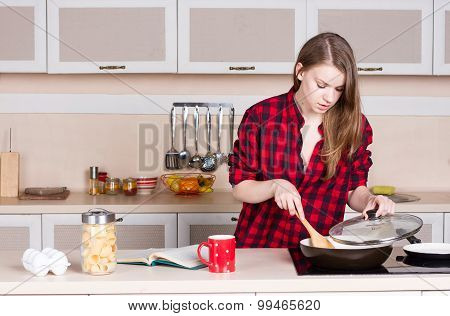 Girl With Long Flowing Hair In A Red Shirt Male Prepares. The Kitchen