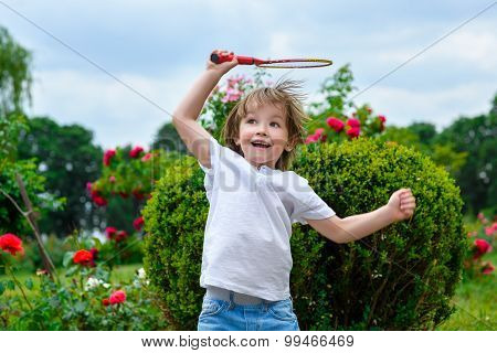 Portrait of happy little boy holding badminton racket and shuttlecock while jumping