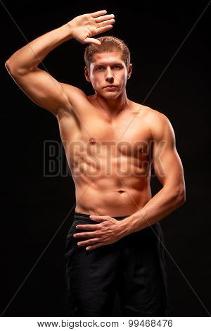 Muscular shirtless sportsman looking at camera with raised hand demonstrating biceps triceps pectora