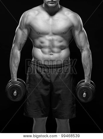 Serious powerful black and white muscular body of young sportsman standing shirtless with black dumb