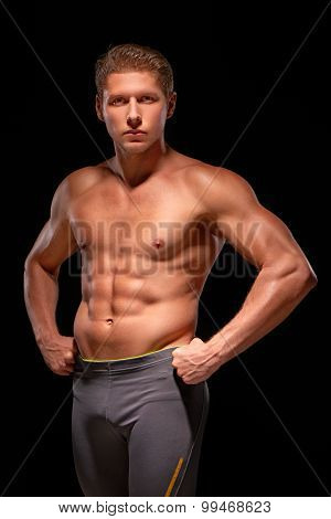 Young muscular handsome shirtless sportsman demonstrating abs pectoral bicep tricep and shoulder mus