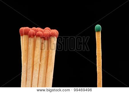 Group of red wooden matches standing with green match isolated on black