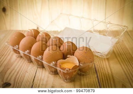 A dozen of eggs in carton, one broken and exposing the yolk