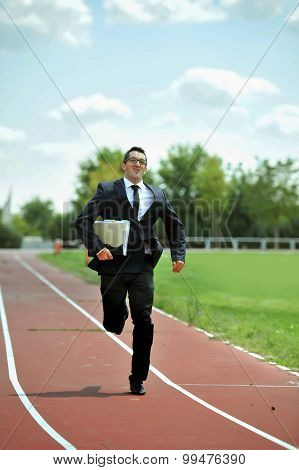 Businessman Running Fast On Athletic Track In Work Stress And Urgency Concept