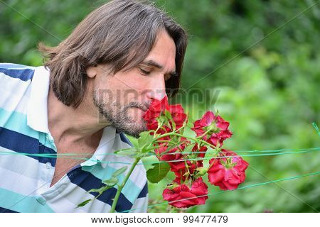 A Man Near The Flowerbeds In The Garden