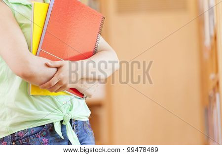 Cropped image of a female student holding notebooks at the library