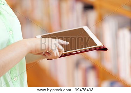 Closeup of a female student using a tablet computer at the library
