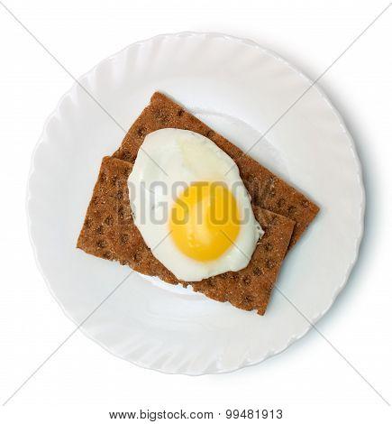 Breakfast: fried egg and crisp bread on plate