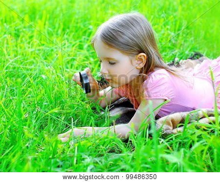 Little Girl Child Looking Through A Magnifying Glass On The Grass