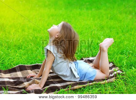 Little Girl Child Lying On The Grass Does Yoga Exercise Outdoors