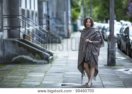Middle-aged woman standing on the street in the evening.
