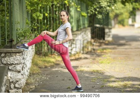 Young sporty woman doing exercise stretching and warm-up before Jogging in park in sunshine on beautiful summer day. Sport fitness model caucasian ethnicity training outdoors. Workout in a Park.