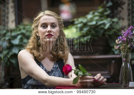 Young lady sitting in summer cafe with a rose in his hand.