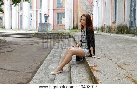 Girl Sitting On The Steps Of The Old Building