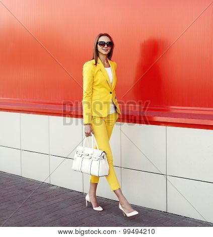 Fashion Elegant Woman Wearing A Yellow Suit Clothes, Sunglasses And Handbag Walking Over Red Backgro