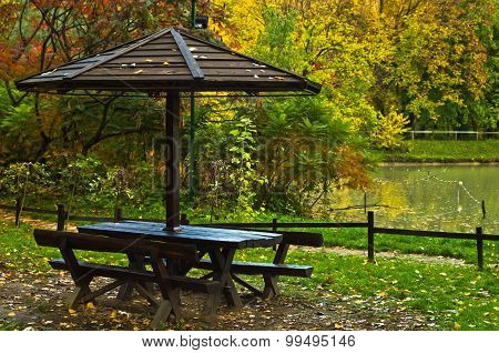 Picnic table by the lake surrounded by the forest in autumn colors, Belgrade
