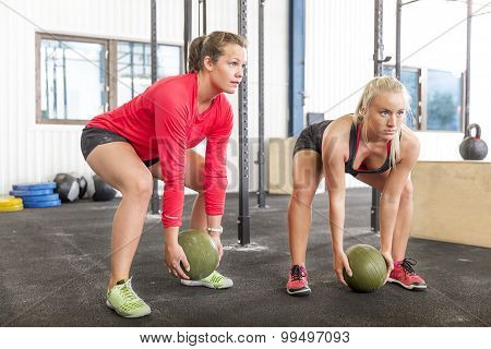 Two women lifts slam balls at the gym