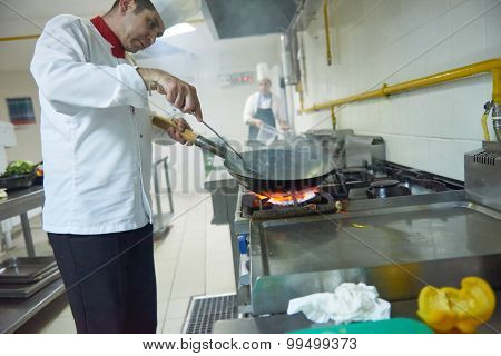 chef in hotel kitchen prepare vegetable  food with fire
